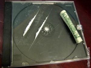 Коробка от компакт-диска с дорожками наркотика и свёрнутая в трубочку долларовая купюра