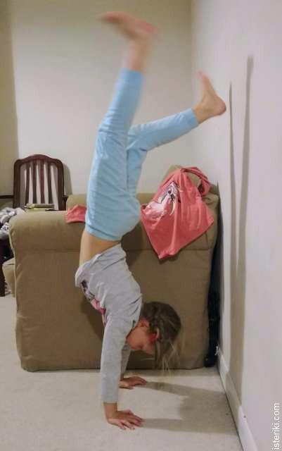 Девочка делает стойку на руках у стены