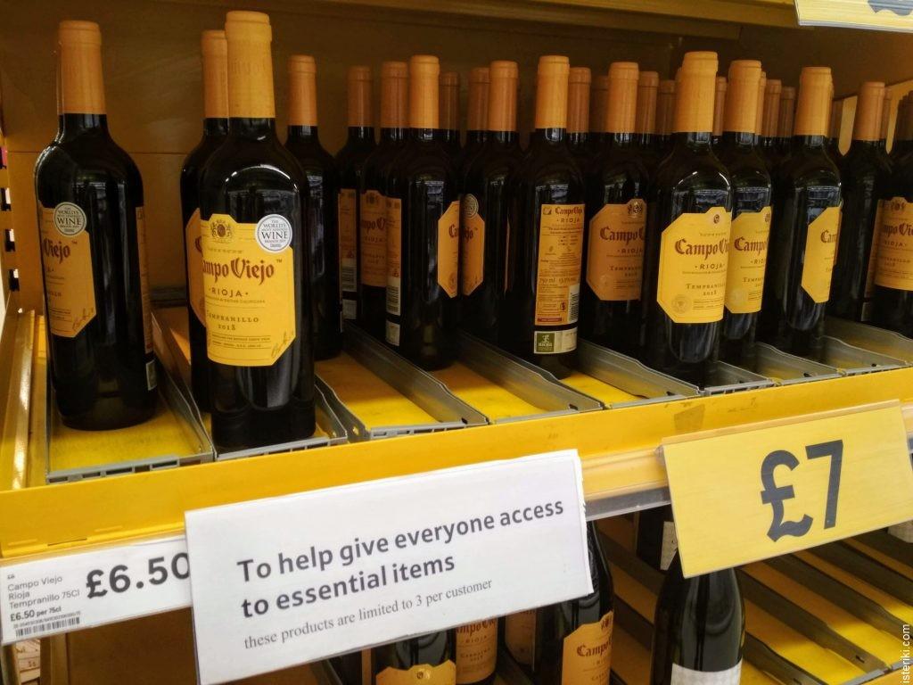 """Полка с вином в магазине. Подпись: """"Чтобы всем досталось товаров первой необходимости, эти продукты отпускаются не более трёх штук на одного покупателя"""""""